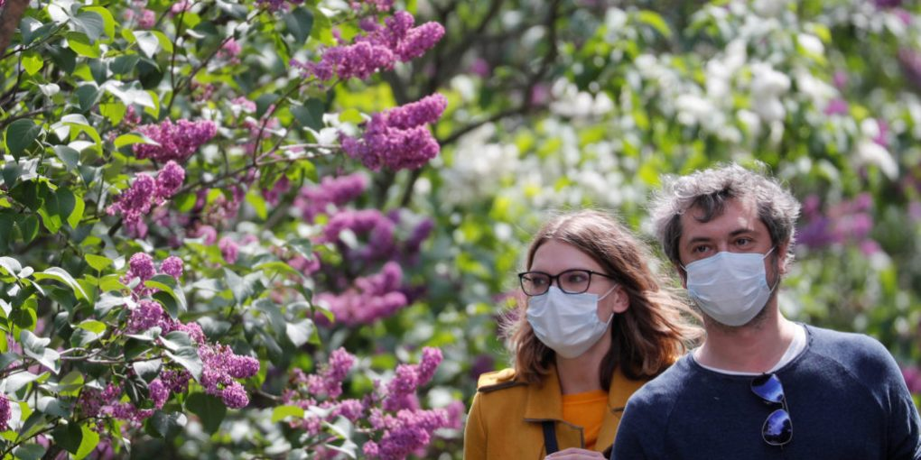 People wearing protective face masks walk past blossoming lilac trees as they visit a botanical garden following the easing of lockdown measures, which were imposed to curb the spread of the coronavirus disease (COVID-19), in Kiev, Ukraine May 18, 2020. REUTERS/Valentyn Ogirenko
